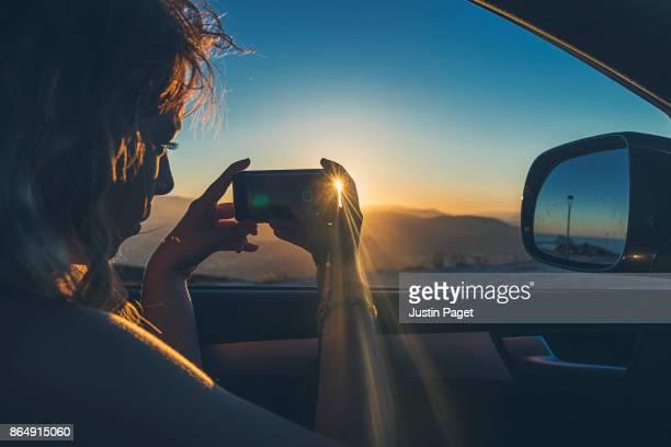 teenage girl taking photo of the sunset from car - mensagem com foto imagens e fotografias de stock