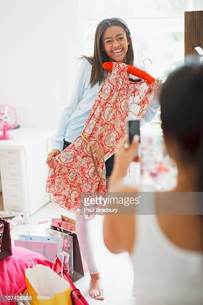 teenage girl taking photograph of friends dress - menselijke leeftijd stockfoto's en -beelden