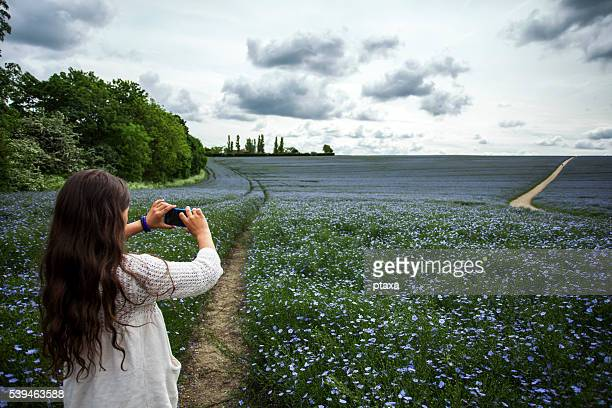 Teenage girl taking picture of flax field with smartphone