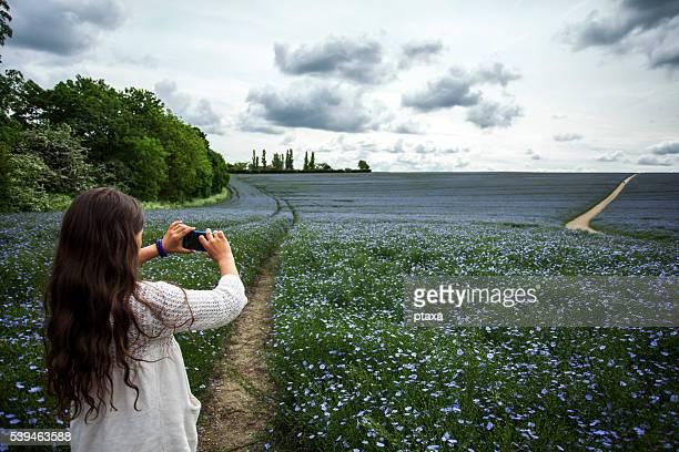 Adolescente prendre photo avec smartphone champ de lin