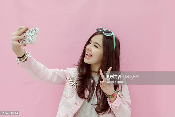 Teenage girl taking picture of herself with smartphone