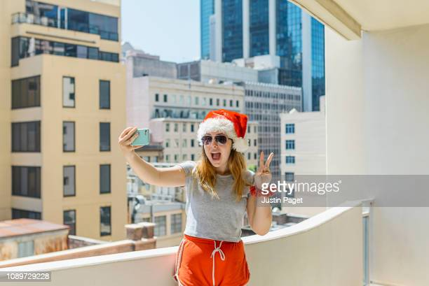 teenage girl taking selfie in santa hat - alternative pose stock pictures, royalty-free photos & images