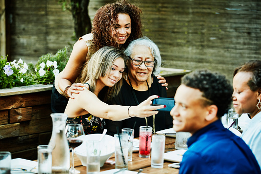 Teenage girl taking selfie with smartphone of mother and grandmother during outdoor family dinner party - gettyimageskorea