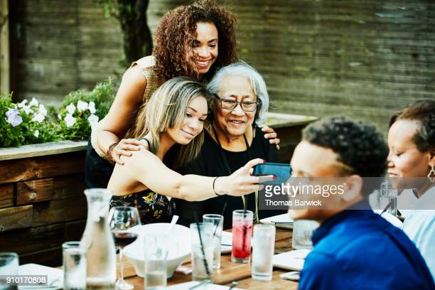 teenage girl taking selfie with smartphone of mother and grandmother during outdoor family dinner party - multigenerational family stock photos and pictures