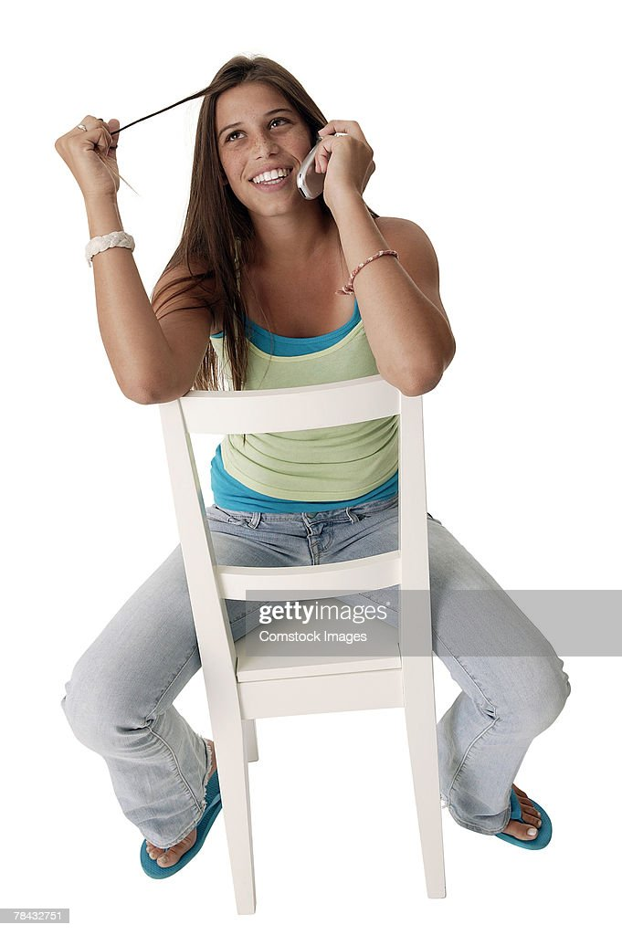 Teenage girl talking on cell phone and twisting hair : Stock Photo