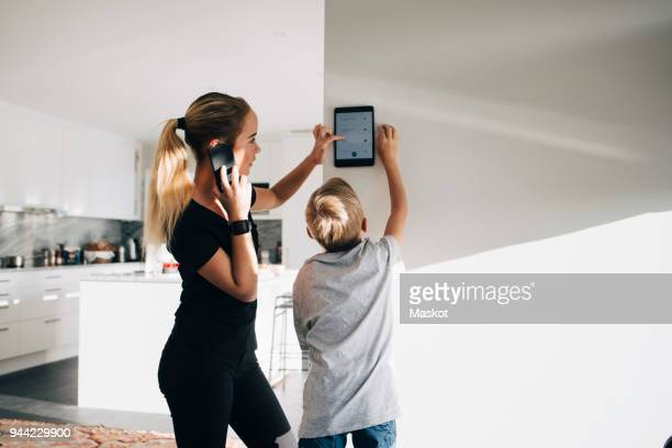 teenage girl talking on phone using digital tablet by brother standing at home - internet delle cose foto e immagini stock