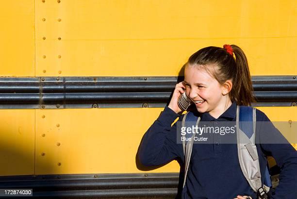 Teenage girl talking on the cellphone outside school bus