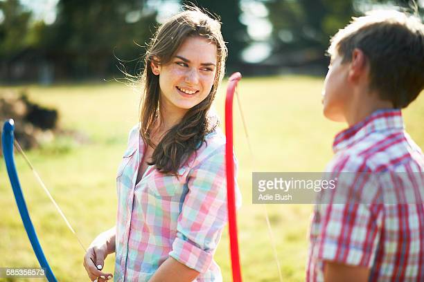 Teenage girl talking to brother whilst practicing archery