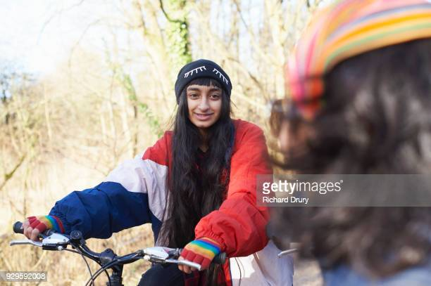 Teenage girl talking to young boy on cycle track