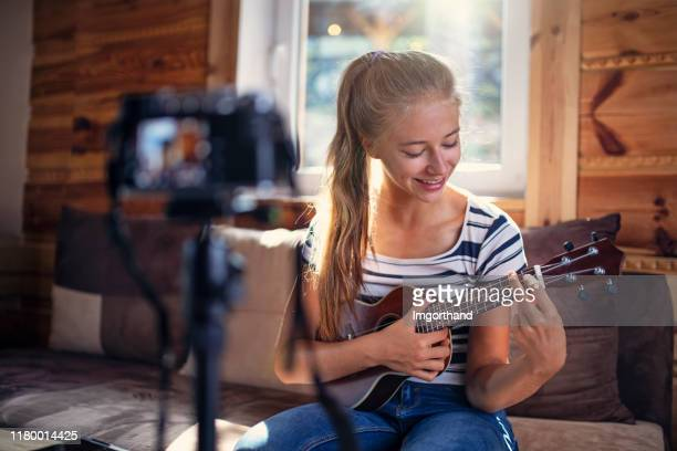 teenage girl teaching how to play ukulele - live streaming stock pictures, royalty-free photos & images