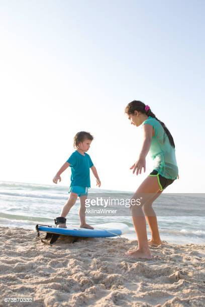 Teenage girl teaching small brother to surf.