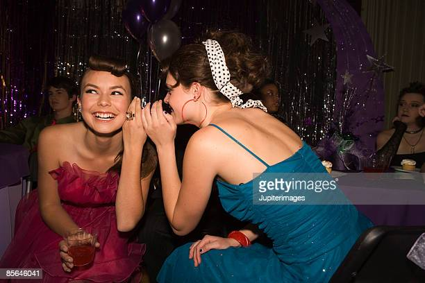 Teenage girl telling a secret to friend at prom