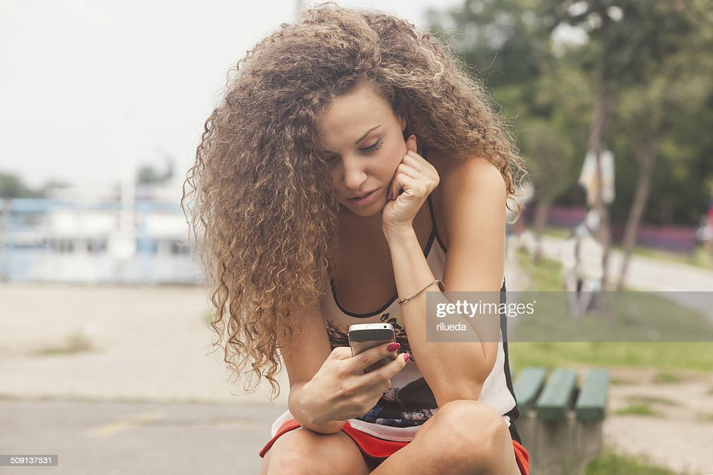 Teenage girl texting on the phone : Stock Photo