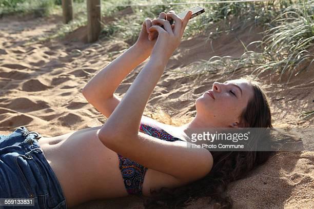 Teenage girl texting SMS laying on beach