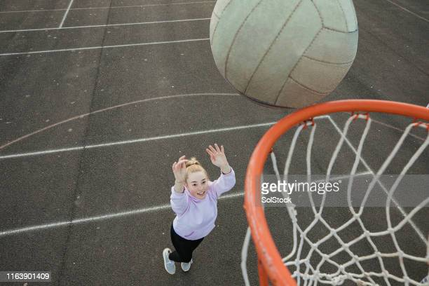 teenage girl throwing a netball - schoolgirl stock pictures, royalty-free photos & images
