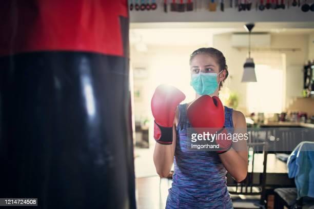 パンチングバッグでボクシングを訓練する十代の少女 - 格闘技 ストックフォトと画像