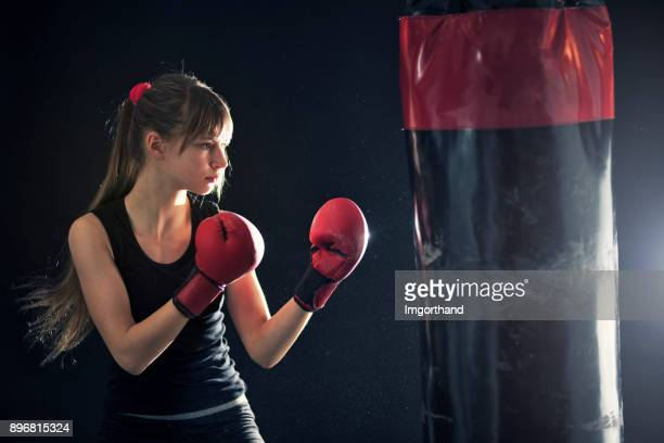 Teenage girl training boxing with punching bag