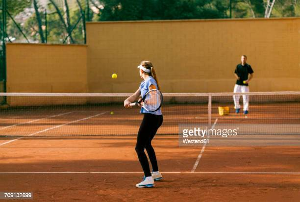 Teenage girl training tennis with her teacher