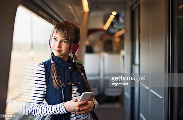 Teenager-Mädchen, die auf Zug und lauschen Sie der Musik aus.