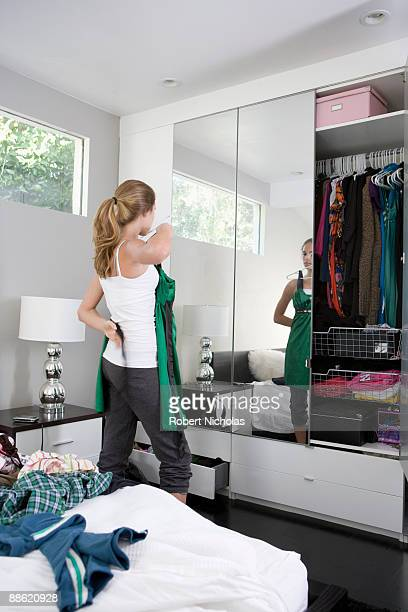 teenage girl trying on clothes in bedroom - girl in mirror stock-fotos und bilder