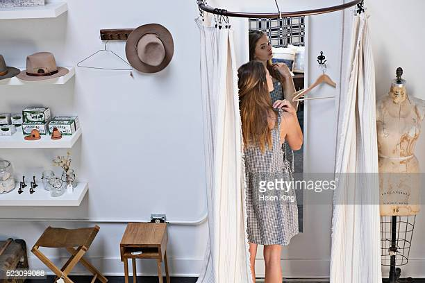 Teenage girl (16-17) trying on dress in fitting room of boutique
