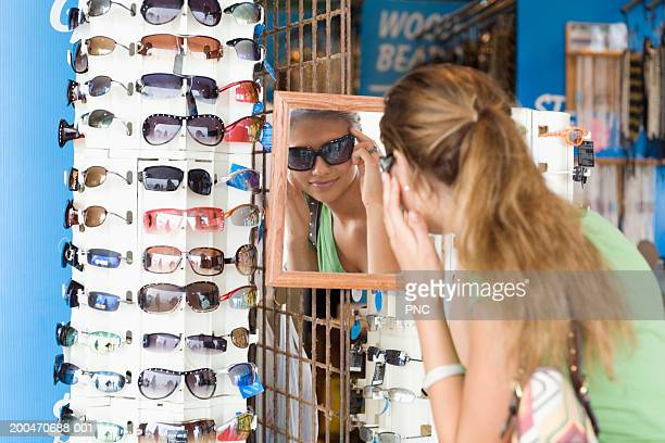 teenage girl (16-18) trying on sunglasses in retail store, rear view - ocean city new jersey stock photos and pictures