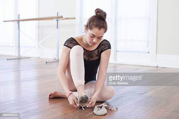teenage girl tying ballet slippers in ballet school - teen girls in tights stock photos and pictures