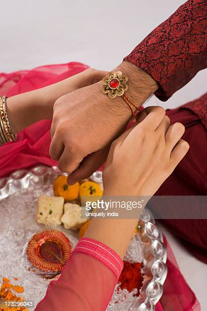 teenage girl tying rakhi on her brother wrist - raksha bandhan stock photos and pictures