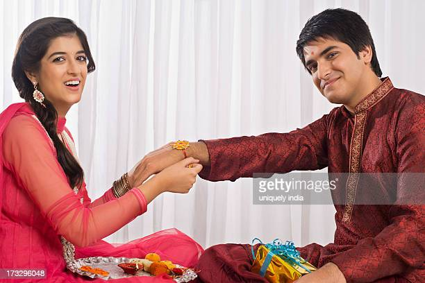 Teenage girl tying rakhi on her brother wrist