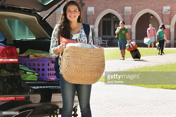 Teenage girl unloading car at college dormitory