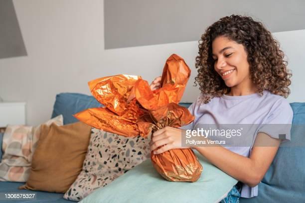 teenage girl unwrapping easter egg sitting on sofa - sentar se imagens e fotografias de stock