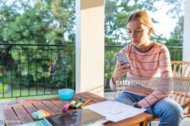 adolescente usando um celular para lição de casa - patio de colegio - fotografias e filmes do acervo