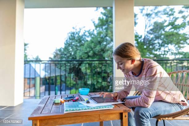 adolescente usando um tablet para trabalho escolar de casa - patio de colegio - fotografias e filmes do acervo