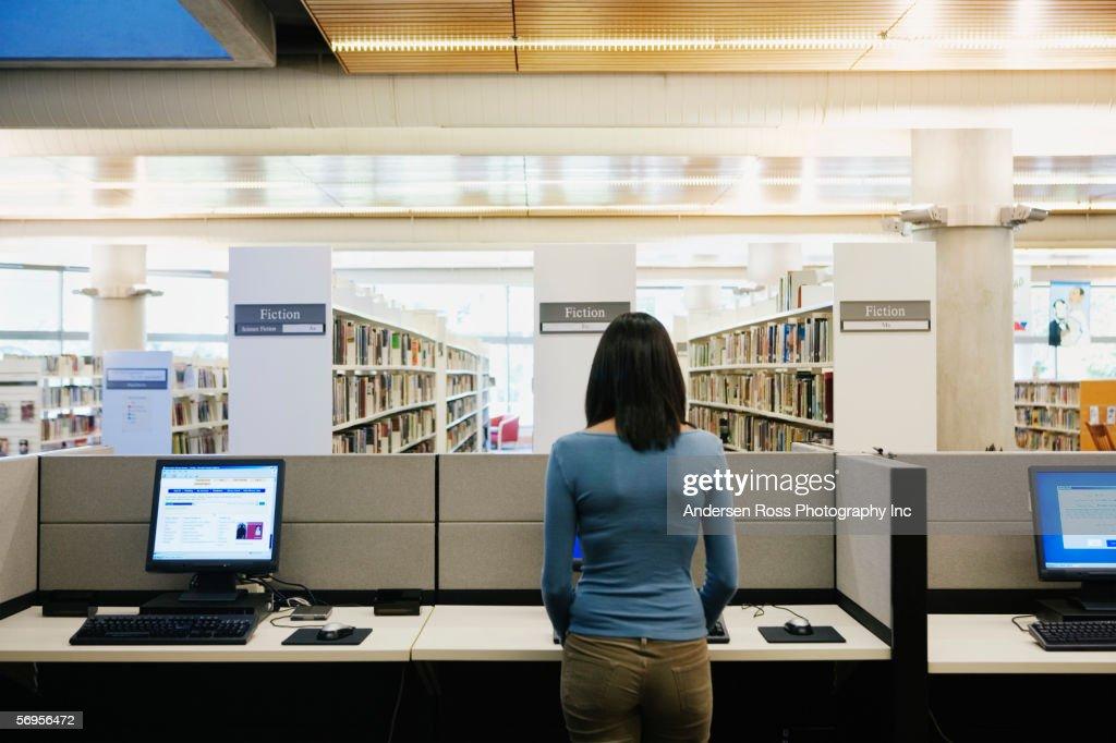 Teenage girl using computer at library : Stock Photo