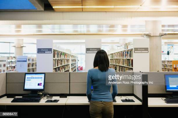 teenage girl using computer at library - indian college girls stock photos and pictures