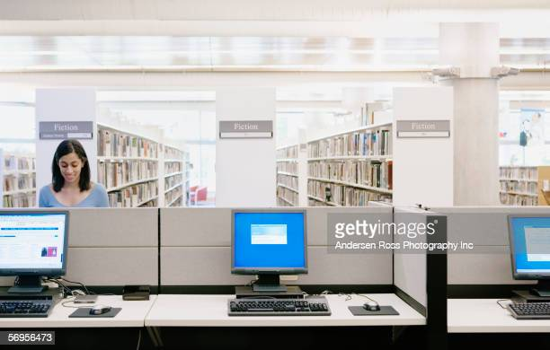 Teenage girl using computer in library