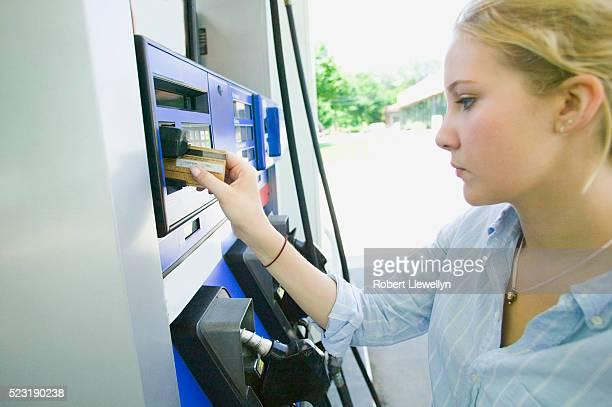 Teenage Girl Using Credit Card at Gas Station