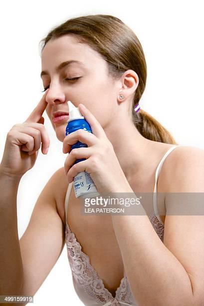 Teenage girl using decongestant