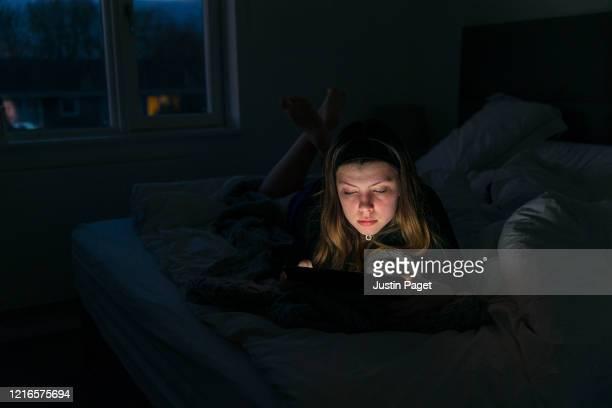 teenage girl using digital tablet in bed - inquadratura fissa foto e immagini stock