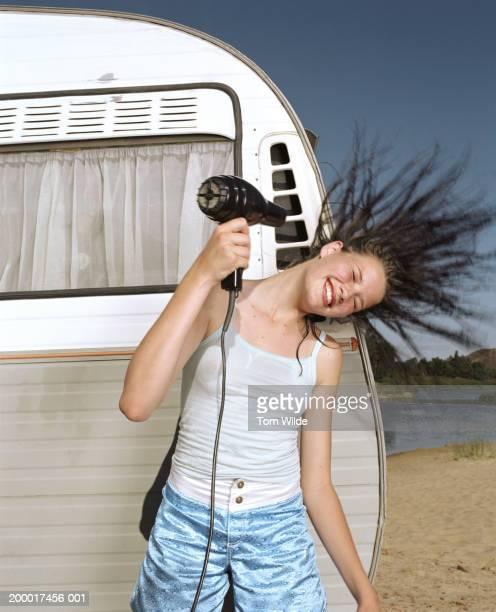 Teenage girl (15-17) using hairdryer by caravan, outdoors