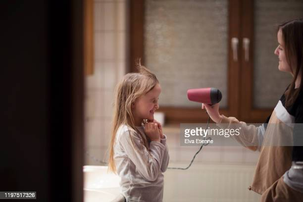 teenage girl using hairdryer to blow dry younger sister's long hair in a bathroom - elektrizität stock-fotos und bilder