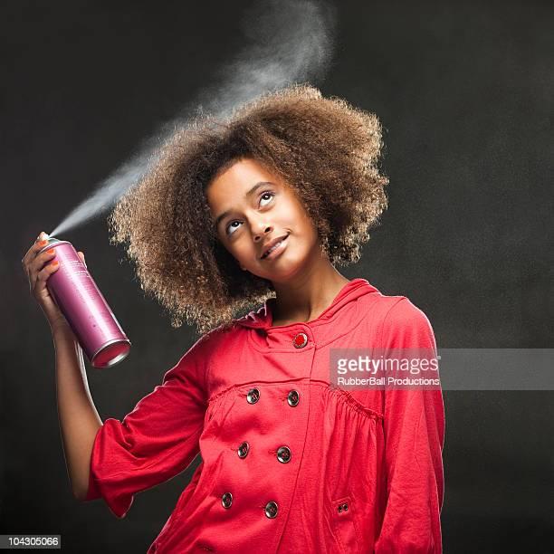 Teenage girl (12-13) using hairspray,studio shot