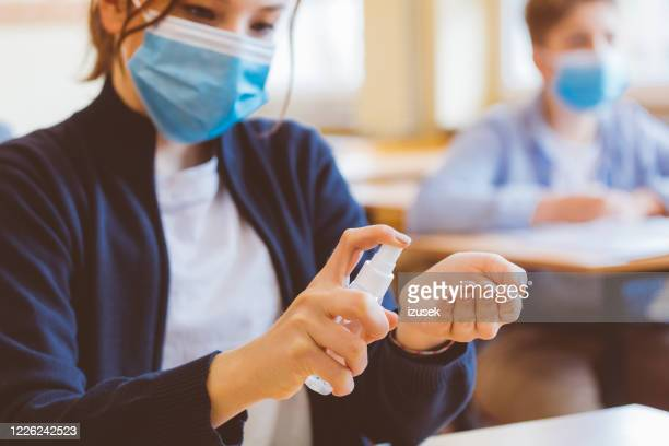 teenage girl using hand sanitizer in the classroom - coronavirus stock pictures, royalty-free photos & images
