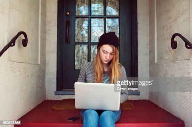 teenage girl using laptop while sitting at house entrance - une seule adolescente photos et images de collection