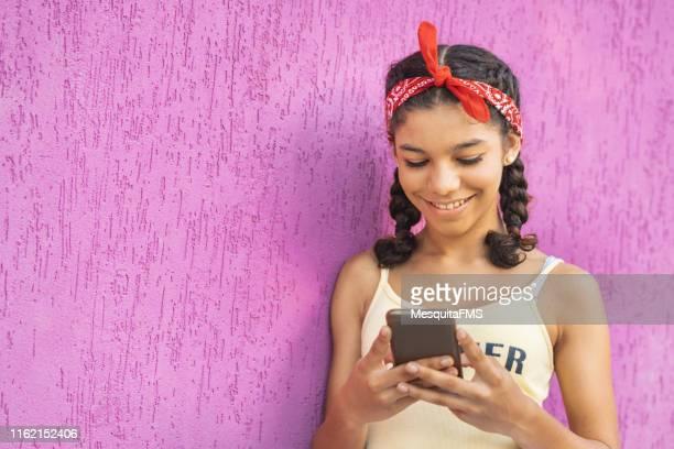adolescente utilisant le téléphone portable sur le fond de lilac - teen webcam photos et images de collection