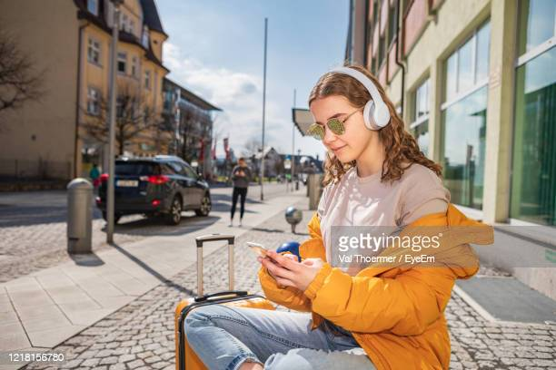 teenage girl using mobile phone on street in city - val thoermer stock-fotos und bilder