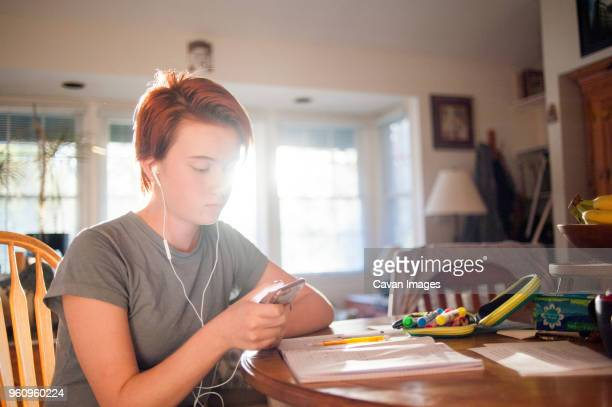 Teenage girl using mobile phone while sitting on chair at home