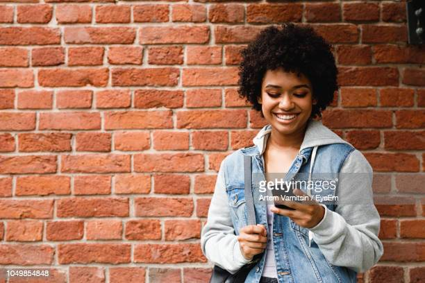 teenage girl using mobile phone while standing against brick wall - teenage girls ストックフォトと画像