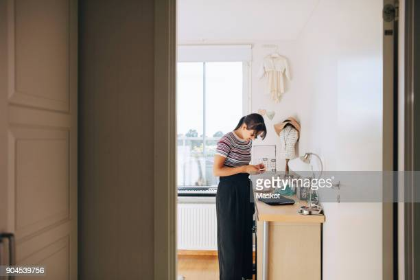 Teenage girl using mobile phone while standing by cabinet in bedroom at home