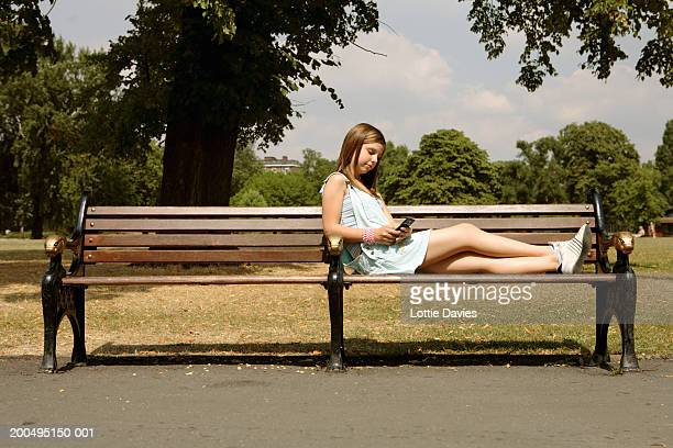 Teenage girl (12-14) using mobile telephone on park bench, side view
